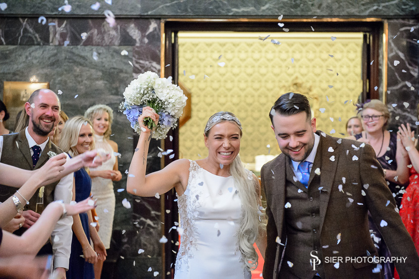 Happy couple in the midst of a confetti shower at a Sheffield Cutlers Hall Wedding